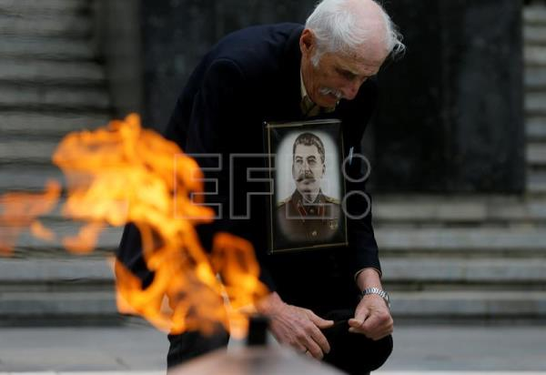 A man with portrait of Soviet dictator Josef Stalin stands in front of the tomb of the unknown soldier during celebrations of the 72nd anniversary of the victory over Nazi Germany in Victory Park, Tbilisi, Georgia, May  9, 2017. EPA/ZURAB KURTSIKIDZE