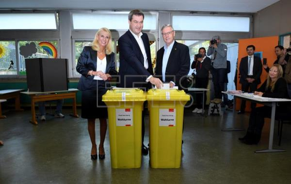 Bavarian Prime Minister Markus Soeder (C) casts his ballot next to his wife Karin Baumueller (L) during the Bavaria state elections at a polling station in Nuremberg, Germany, Oct. 14, 2018. EPA-EFE/CLEMENS BILAN
