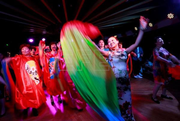 Volunteers of the Parents and Friends of Lesbians and Gays (PFLAG) organization dance with rainbow scarves and costumes during a closing ceremony for the 10th National PFLAG conference held on a cruise en route back to Shanghai, China, June 17, 2017. EPA/HOW HWEE YOUNG