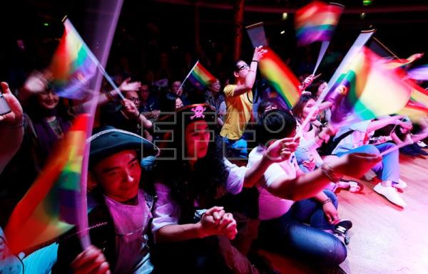 LGBT (lesbian, gay, bisexual and transgender) members of the audience wave rainbow-colored flags during the opening of the 10th National PFLAG conference on a cruise organised by the Parents and Friends of Lesbians and Gays (PFLAG) organization en route back to Shanghai, China, June 17, 2017. EPA/HOW HWEE YOUNG