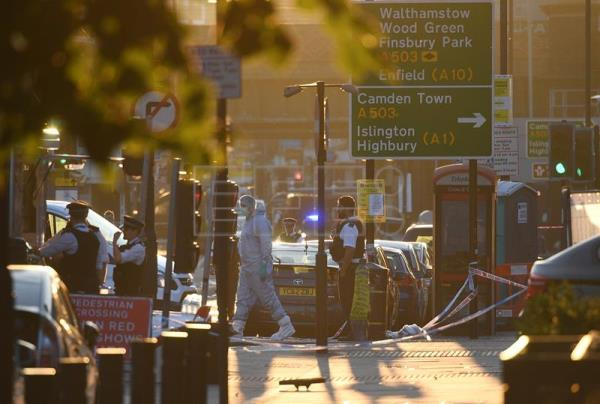 Police officers stand guard as a member of a forensic team works inside the cordon near Finsbury Park, after a van collision incident in north London, Britain, 19 June. EFE