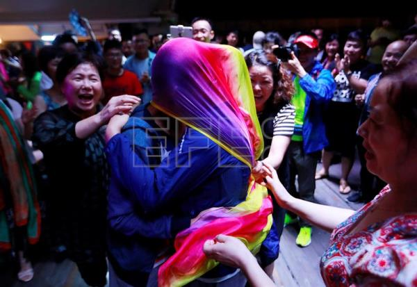 A gay couple kiss under a rainbow-colored scarf during a party after a LGBT (lesbian, gay, bisexual and transgender) mass wedding organized by the Parents and Friends of Lesbians and Gays (PFLAG) organization on a cruise en route back to Shanghai, China, June 17, 2017. EPA/HOW HWEE YOUNG