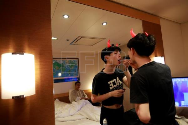 Chinese gay couple Huhu (R) and Wang Yunshen are reflected in a mirror in their cabin room as Huhu does his make up on a cruise organised by the Parents and Friends of Lesbians and Gays (PFLAG) organization en route back to Shanghai, China, June 17, 2017. EPA/HOW HWEE YOUNG
