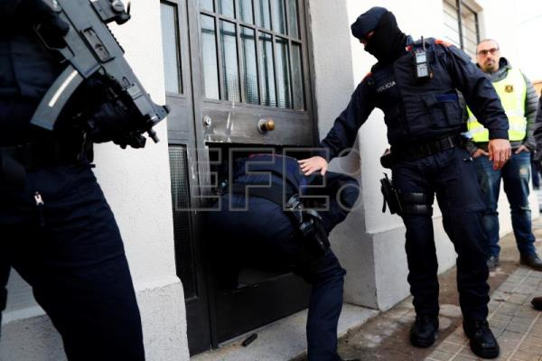 Mossos d'Esquadra agents entering a building during an operation against the Hells Angels in Sabadell, Spain, Feb,. 7, 2018. EPA-EFE/Alejandro García