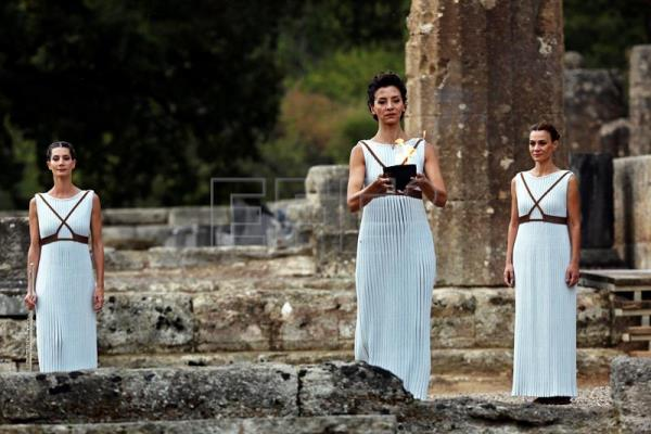 flame lighting olympics. greek actress katerina lechou (c), in the role of high priestess, flame lighting olympics