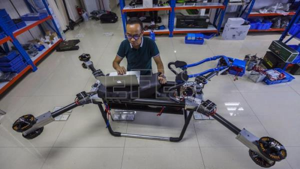 Zhao Deli adjusts his self-made 'flying scooter' at his office and workshop in Dongguan, Guangdong Province, China, Aug. 12, 2018 (issued Aug. 16, 2018). EPA-EFE/Aleksandar Plavevski