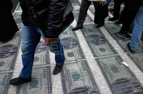 Iranians walk over a banner depicting US dollar banknotes during an anti-US demonstration marking the 39th anniversary of US Embassy takeover, in front of the former US embassy in Tehran, Iran, Nov. 4, 2018. EPA/ABEDIN TAHERKENAREH