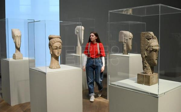 "A staff member walks among Modigliani's ""Women's Heads"" (1911-12) sculptures at the Tate Modern in London, Britain, Nov. 21, 2017. EPA/ANDY RAIN"