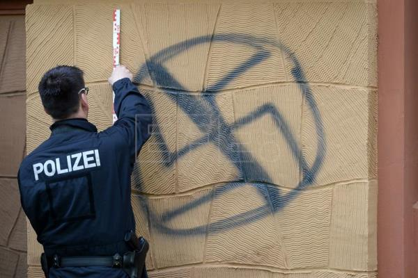 A file image from Apr. 26, shows a police securing evidence of a swastika sprayed onto a wall in Potsdam, Germany.  PA/RALF HIRSCHBERGER