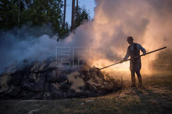 Pit apprentice Valtteri Ylosjarvi tends to the tar pit during his wake shift on the grounds of the Yli-Kirra Outdoor Agricultural Museum in Punkalaidun, Finland, June 29, 2017. EPA/MARKKU OJALA