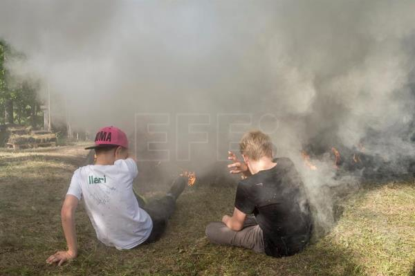 Young spectators sit in a cloud of smoke of a pine tar pit during its lighting ceremony on the grounds of the Yli-Kirra Outdoor Agricultural Museum in Punkalaidun, Finland, June 29, 2017. EPA/MARKKU OJALA