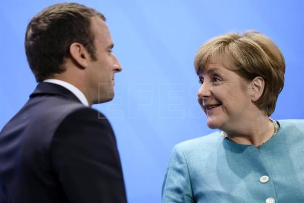 French President Emmanuel Macron (L) and German Chancellor Angela Merkel say goodbye after a joint press conference during the European G-20 leaders preparatory meeting at the Chancellery in Berlin, Germany, June 29, 2017. EPA/CLEMENS BILAN