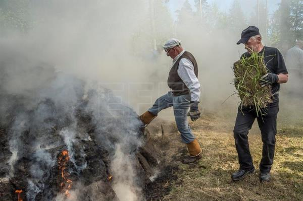 80-year-old Tar Pit Master Valdemar 'Valte' Nummelin (L) checks a pine tar pit after lighters have ensured that the burning has started evenly around the pit on the grounds of the Yli-Kirra Outdoor Agricultural Museum in Punkalaidun, Finland, June 29, 2017. EPA/MARKKU OJALA