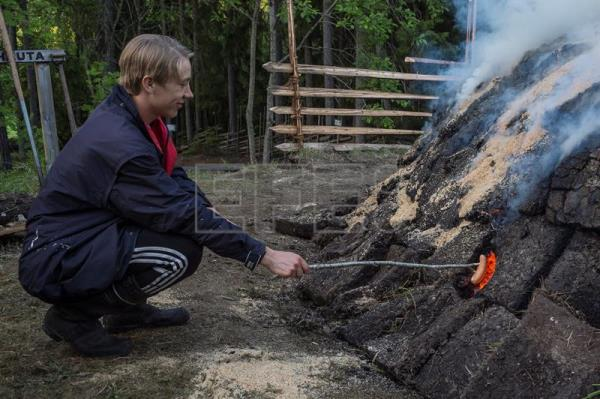 Pit apprentice Valtteri Ylosjarvi barbecues a sausage over a pine tar pit on the grounds of the Yli-Kirra Outdoor Agricultural Museum in Punkalaidun, Finland, June 29, 2017. EPA/MARKKU OJALA