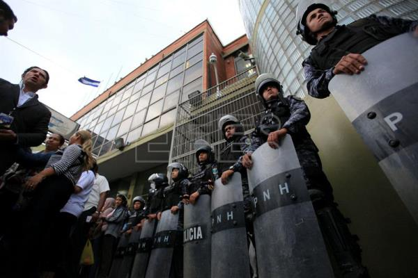 Honduran police members stand guard while  governing National Party sympathizers demand the registration of President Juan Orlando Hernandez to participate in the next elections, in front of the National Elections Tribunal, in Tegucigalpa, Honduras on December 14, 2016. EFE / Gustavo Amador