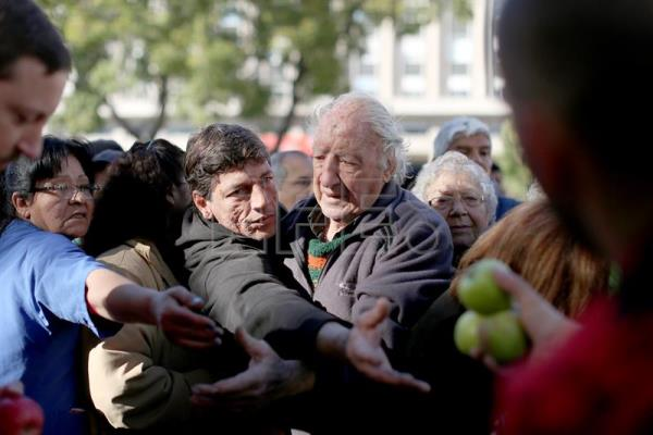 Hundreds of people line up to get fruits in the Plaza de Mayo in Buenos Aires, Argentina, 23 August 2016. fruit growers of the Argentinian southern province of Rio Negro distribute fruit in the Plaza de Mayo in protest for the situation in their sector. EPA / David Fernández