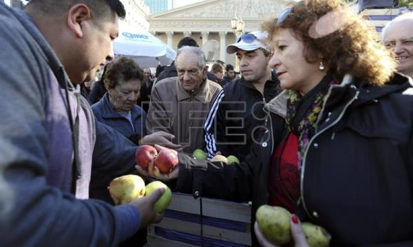 Farmers from the southern Rio Negro province distribute their fruit for free, on the Plaza de Mayo in Buenos Aires, Argentina, 23 August 2016. The farmers gave out their produce for free to protest against high production costs. EPA/David Fernandez