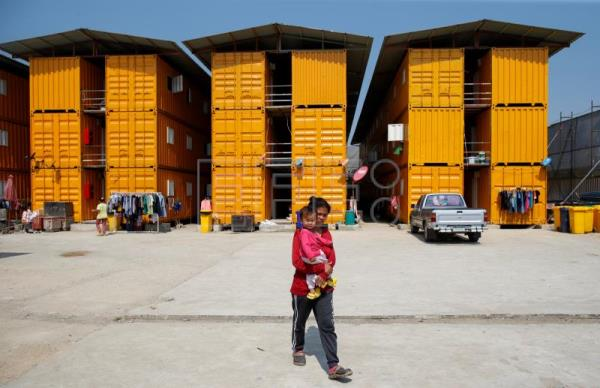 A migrant worker holds her daughter while bringing her to a school made of refurbished shipping containers at a container village in Bangkok, Thailand, Jan. 18, 2018. EPA-EFE/RUNGROJ YONGRIT