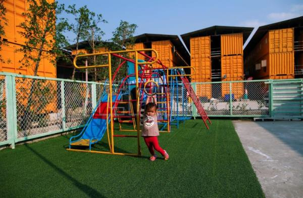 A Cambodian migrant worker's chilad plays on a playground outside a school made of refurbished shipping containers at a container village in Bangkok, Thailand, Jan. 18, 2018. EPA-EFE/RUNGROJ YONGRIT