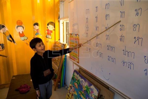 Kim Pol, 14, son of a Cambodian migrant worker, practices basic Thai language inside a school made of refurbished shipping containers at a container village in Bangkok, Thailand, Jan. 18, 2018. EPA-EFE/RUNGROJ YONGRIT