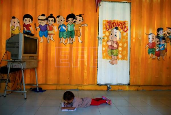 The child of a migrant worker draws a sketch inside a school made of refurbished shipping containers at a container village in Bangkok, Thailand, 18 January 2018. EPA-EFE/RUNGROJ YONGRIT