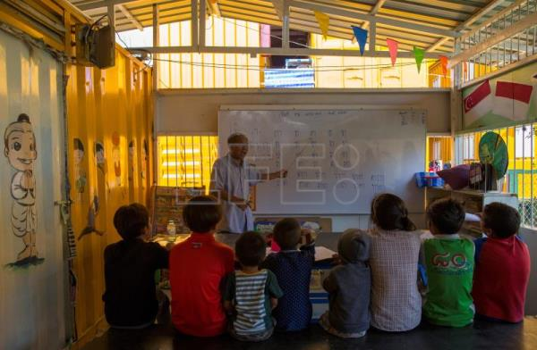Thai teacher Pairoj Jantawong (background) teaches basic Thai language lessons to migrant workers' children inside a school made of refurbished shipping containers at a container village in Bangkok, Thailand, Jan. 18, 2018. EPA-EFE/RUNGROJ YONGRIT