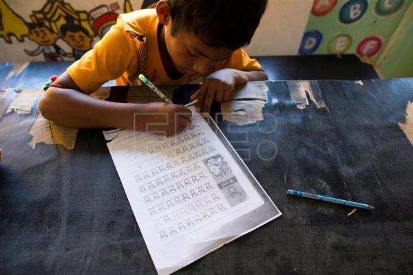 The child of a migrant worker from Cambodia practices basic Thai language during a class inside a school made of refurbished shipping containers at a container village in Bangkok, Thailand, Jan. 18, 2018. EPA-EFE/RUNGROJ YONGRIT
