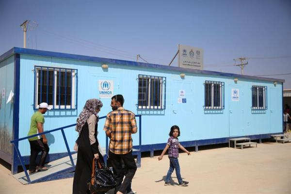 Syrian refugees walk past the newly opened Zaatari office for employment, at the Zaatari refugee camp, some 80 km East of Amman, Jordan, Sept. 11, 2017. EPA/AMEL PAIN