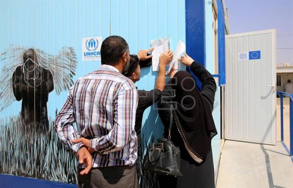 Syrian refugees look for their names on the list of newly delivered working permits outside the newly opened Zaatari office for employment, at the Zaatari refugee camp, some 80 km East of Amman, Jordan, Sept. 11, 2017. EPA-EFE/AMEL PAIN