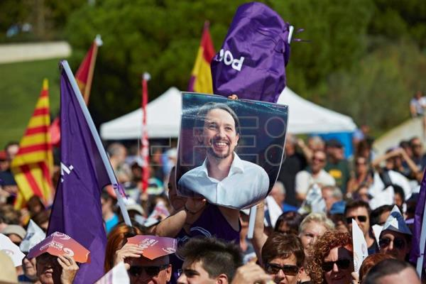 People gather and hold flags and a poster with the image of Spanish party 'Podemos' leader, Pablo Iglesias, during a political event organized by Catalunya en Comu party on the occasion of the National Day of Catalonia (Diada), in Barcelona, Spain, Sept. 11, 2017. EPA-EFE/Alejandro Garcia