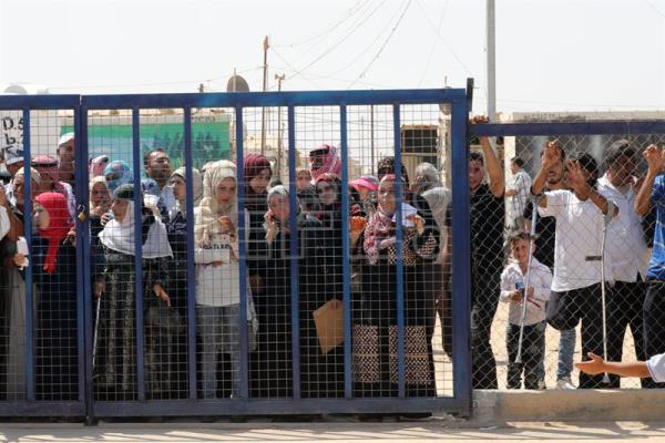 Syrian refugees wait for their turn to enter services facility area to apply for employment, temporary exits, registration and return to Syria, permits or documents at the Zaatari refugee camp, some 80 km East of Amman, Jordan, Sept. 11, 2017. EPA-EFE/AMEL PAIN