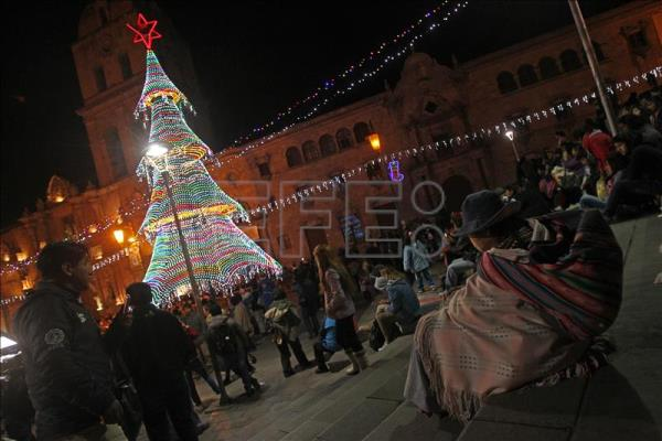 People attend the Christmas tree lighting ceremony in front of city hall on Wednesday in La