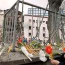 A woman lights candles and places flowers near the headquarters of Serbia's Radio Televizija Srbije (RTS) during a protest march in Belgrade Saturday, Apr. 24, 1999. EPA-EFE FILE/VLADIMIR VASIN