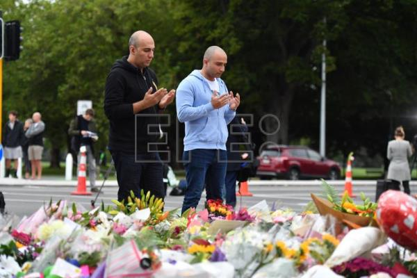 Two men pray at a flower memorial near the Al Noor Masjid on Deans Rd in Christchurch, New Zealand, Mar. 16, 2019. EPA-EFE/MICK TSIKAS AUSTRALIA AND NEW ZEALAND OUT