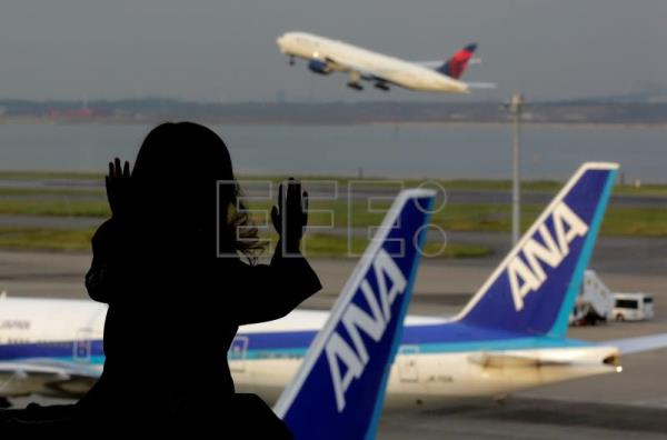 A girl watches airplanes of All Nippon Airways Co., Ltd. (ANA) and a plane taking off at Tokyo International Airport at Haneda in Tokyo, Japan, Oct. 31, 2016. EPA-EFE FILE/KIMIMASA MAYAMA