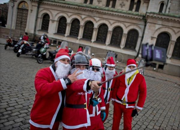 Motorcyclists wearing Santa Claus outfits take a selfie as they attend a Bulgarian Vespa Club gathering in Sofia, Bulgaria, Dec. 15, 2018. EPA-EFE/VASSIL DONEV