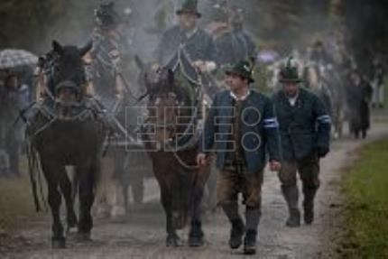 Bavarian town defies rain to honor saint with horse-drawn carriage procession