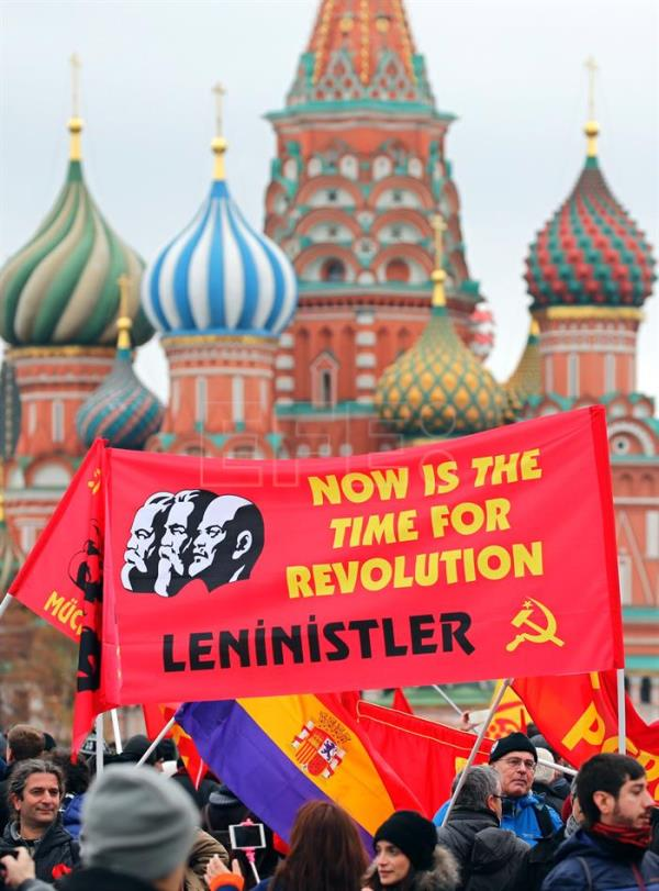 Russian Communists carry Soviet red flags and a banner 'Now is the time for Revolution' as they attend a ceremony of laying flowers to the Lenin's Mausoleum on the Red Square in Moscow, Russia. EFE