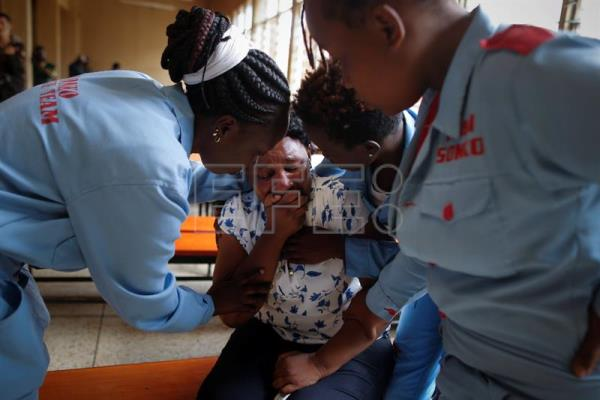 A family member of the student is helped by volunteer workers as she breaks down and cries at Moi Girls School in Nairobi, Kenya, 02 September 2017. EFE