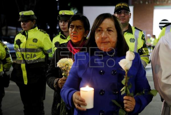 Citizens and police hold candles during a vigil at the Francisco de Paula Santander General Police Cadet School in Bogota, Colombia, Jan. 17, 2019. EPA-EFE/LEONARDO MUNOZ