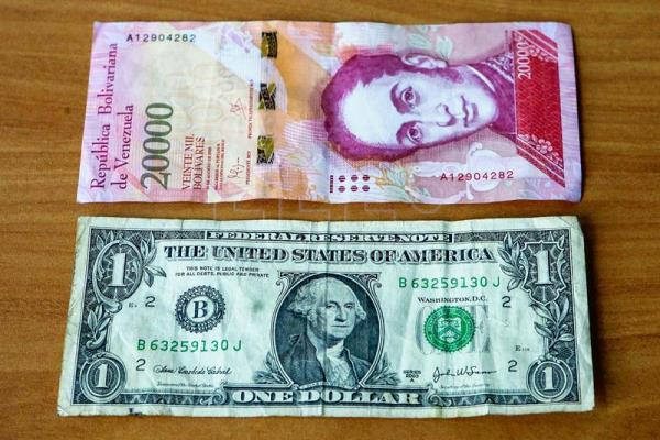 View Of A Us One Dollar Bill Next To 20 000 Bolivares The Gest