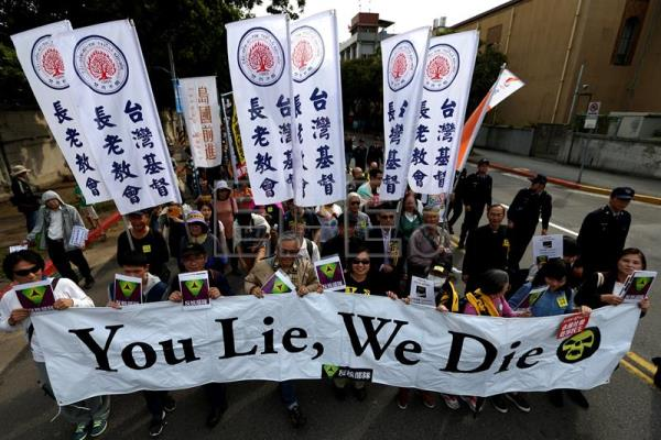 Taiwanese protesters carry an anti-nuclear power plant placard as they march at the street during a protest in Taipei, Taiwan, 11 March 2017. EPA/RITCHIE B. TONGO