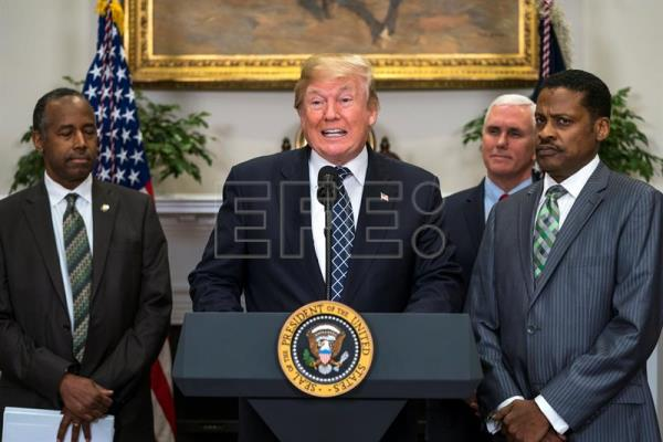 US President Donald J. Trump (C), alongside President for the Martin Luther King, Jr. Center Isaac Newton Farris, Jr.(R) and Secretary of Housing and Urban Development Ben Carson (L), speaks before signing a proclamation to honor Dr. Martin Luther King, Jr. Day in the Roosevelt Room of the White House in Washington, DC, USA Jan. 12, 2018. EPA-EFE/JIM LO SCALZO