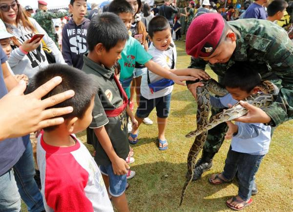 A Thai soldier places a python snake over a child as part of the National Children's Day events at a military base in Bangkok, Thailand, 13 January 2018. EFE