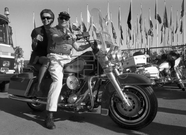 US tycoon Malcolm Forbes (R), with the Countess of Romanones riding pillion (L), driving his Harley Davidson bike at La Cartuja area in Seville. May 1, 1989. EPA-EFE(FILE)/Julio Munoz/fs
