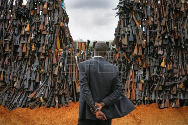 A government official looks at a pile of illegal firearms before it was set alight at a field in Ngong, in the outskirts of the capital Nairobi, Kenya, 15 November 2016. EPA/DAI KUROKAWA