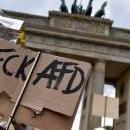 A man holds a cardboard reading 'FCK AFD' to protest against a demonstration of the 'Alternative for Germany' (AfD) party at the Brandenburg Gate in Berlin, Germany, May 27, 2018. EPA-EFE/MARKUS HEINE