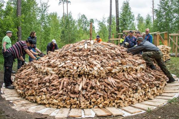 Villagers and tar heritage enthusiasts stack chopped 'tervas' wood to a pine tar pit on the grounds of the Yli-Kirra Outdoor Agricultural Museum in Punkalaidun, Finland, June 27, 2017. EPA/MARKKU OJALA