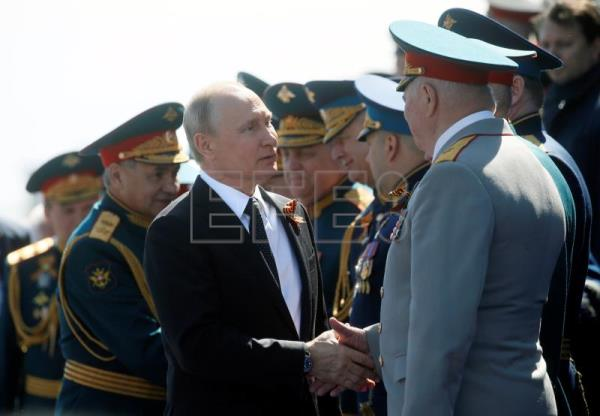 Russian President Vladimir Putin (C) shakes hands with generals after the Victory Day parade in Moscow, Russia, May 9, 2018. EPA-EFE/MAXIM SHIPENKOV/POOL