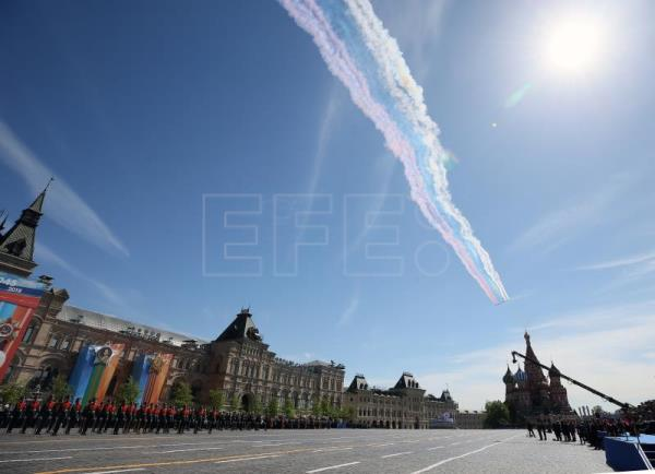 Russian combat planes leave smoke trails of the colors of the Russian national flag as they fly at the end of the Victory Day parade in Moscow, Russia, May 9, 2018. EPA-EFE/MAXIM SHIPENKOV/POOL